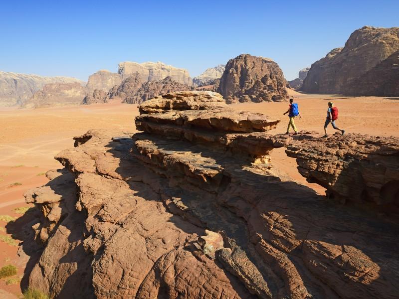 Couple hiking at Rock Arch, Al Borg Alsagheer, Wadi Rum, Jordan, Middle East, Orient - Model Released -