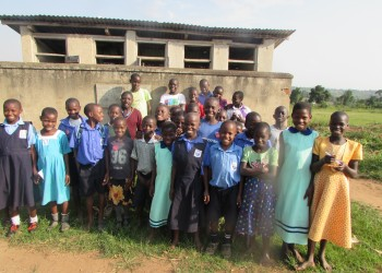 Pupils posinginfront of the five stanced latrine shared by pupils, teachers and the nearby community.